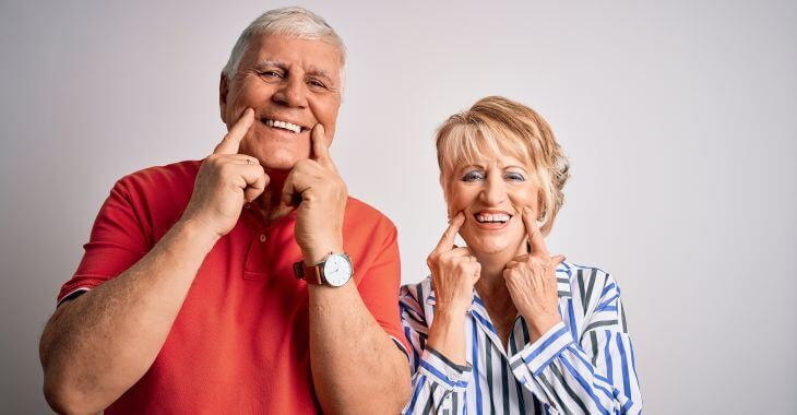 Smiling senior man and woman pointing at their teeth after dental implants treatment.