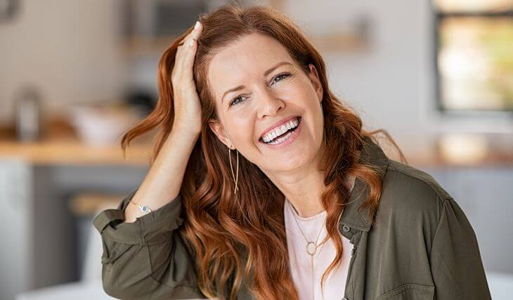 Happy middle-aged woman showing her nice teeth after dental implant treatment in her smile.