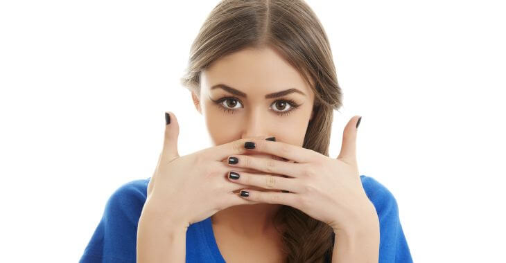 Teenage girl covering her mouth with hands.