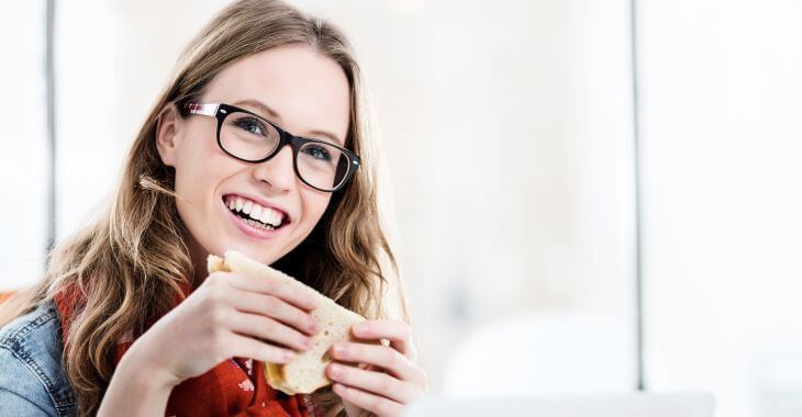 A cheerful young woman with glasses eating a sandwich.