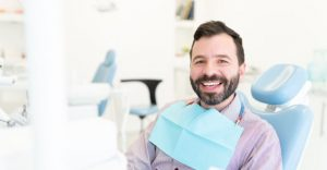A relaxed satisfied man in a dental chair after root canal procedure.