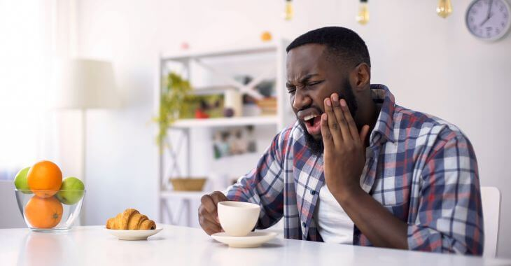 Afro-American man feeling severe tooth pain after having a sip of hot coffee.