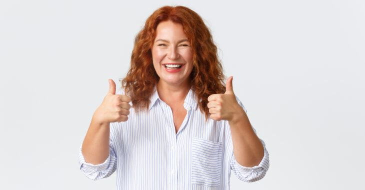 A happy woman after dental implant procedure showing her thumbs up.
