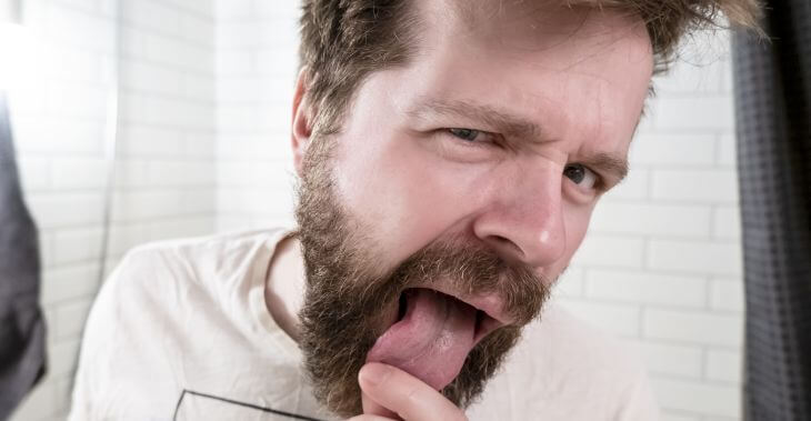 A man looking at his scalloped tongue in the mirror.