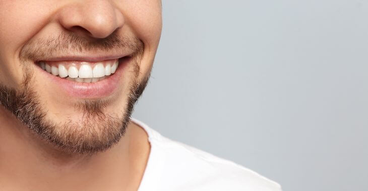 A man showing his perfect teeth after dental implant treatment in his smile.