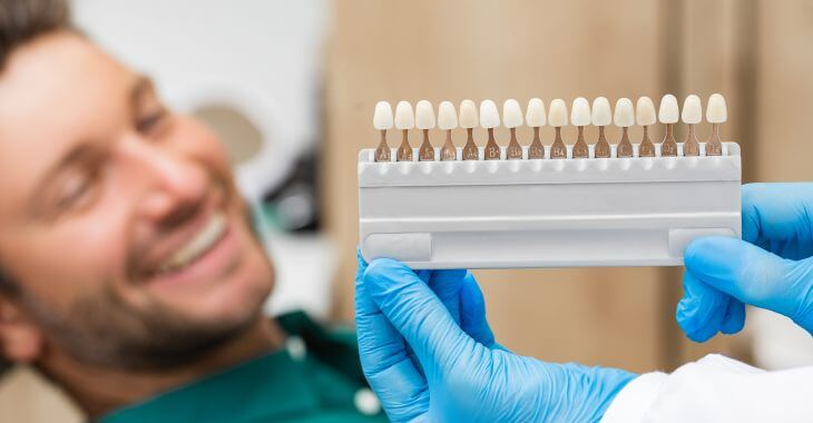 A happy man in a dental chair during veneer color matching.
