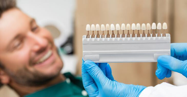 A man in a dental chair before a veneer replacement.