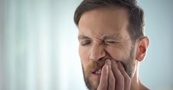 A man with dental pain caused by gum disease.