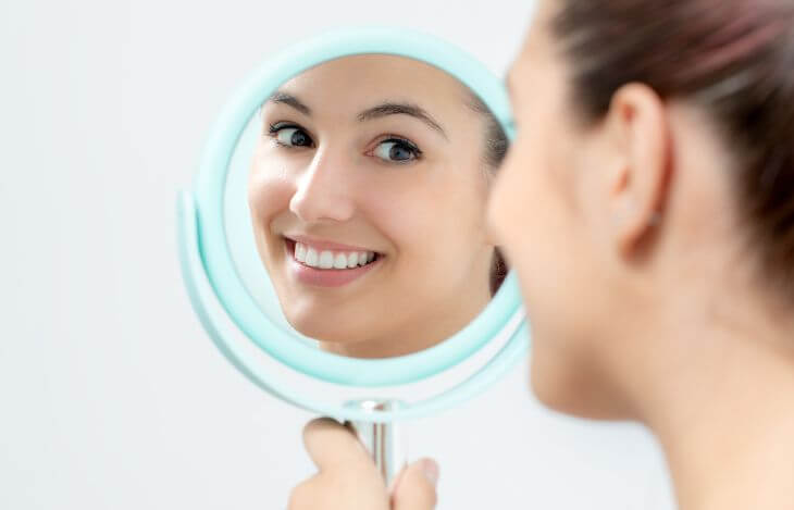 Girl looking at her teeth in a mirror.