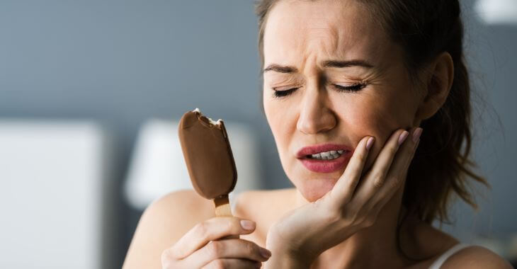 A woman with ice-cream suffering dental pain due to teeth sensitivity to cold.