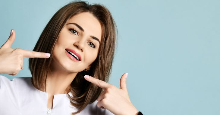 Woman pointing at her perfect teeth.