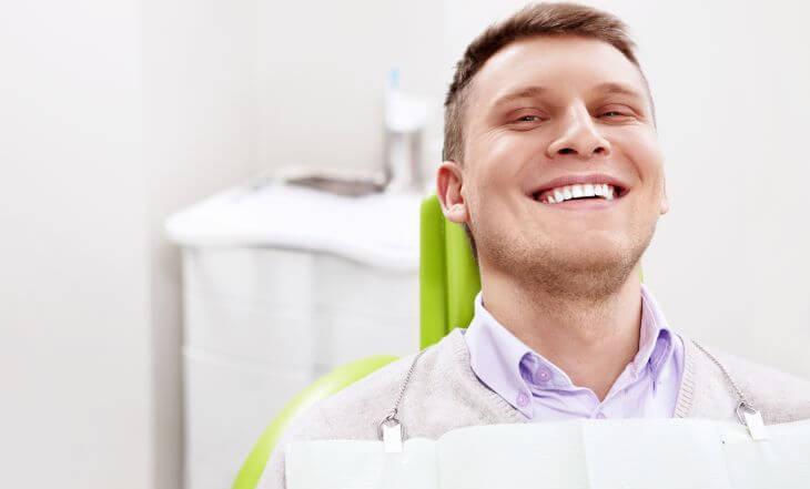 A happy man in a dental chair after dental veneers procedure.