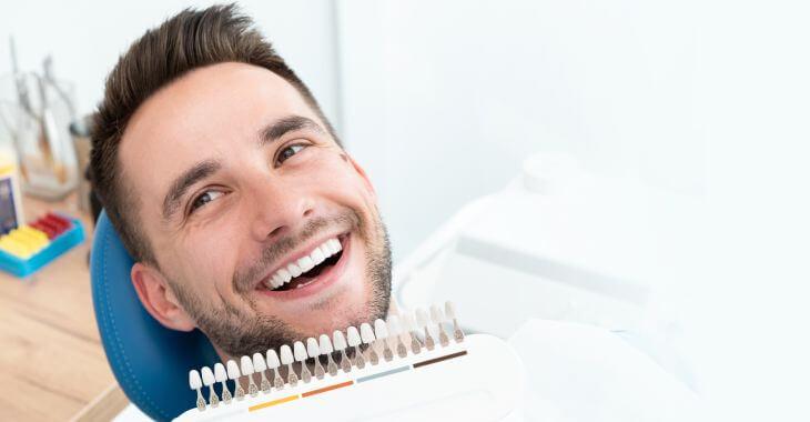 Satisfied man in a dental chair after teeth bleaching procedure.