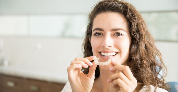 A woman with perfect teeth holding a dental retainer.