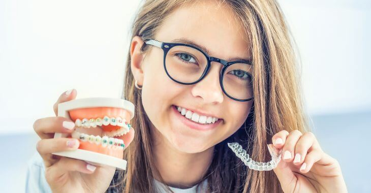 A teenage girl holding a dental model with braces in one hand and a retainer in the second hand.
